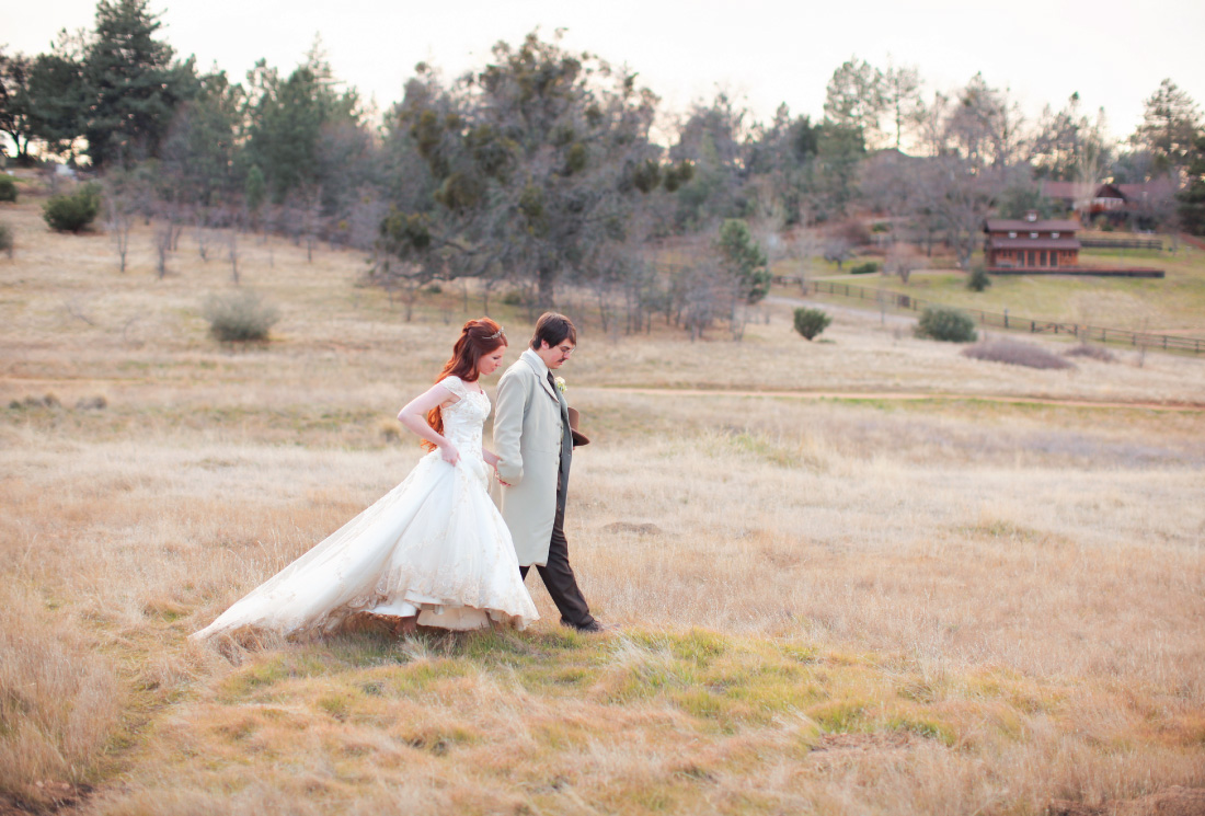 bride and groom strolling in an open meadow at the Julian Meadow View Inn