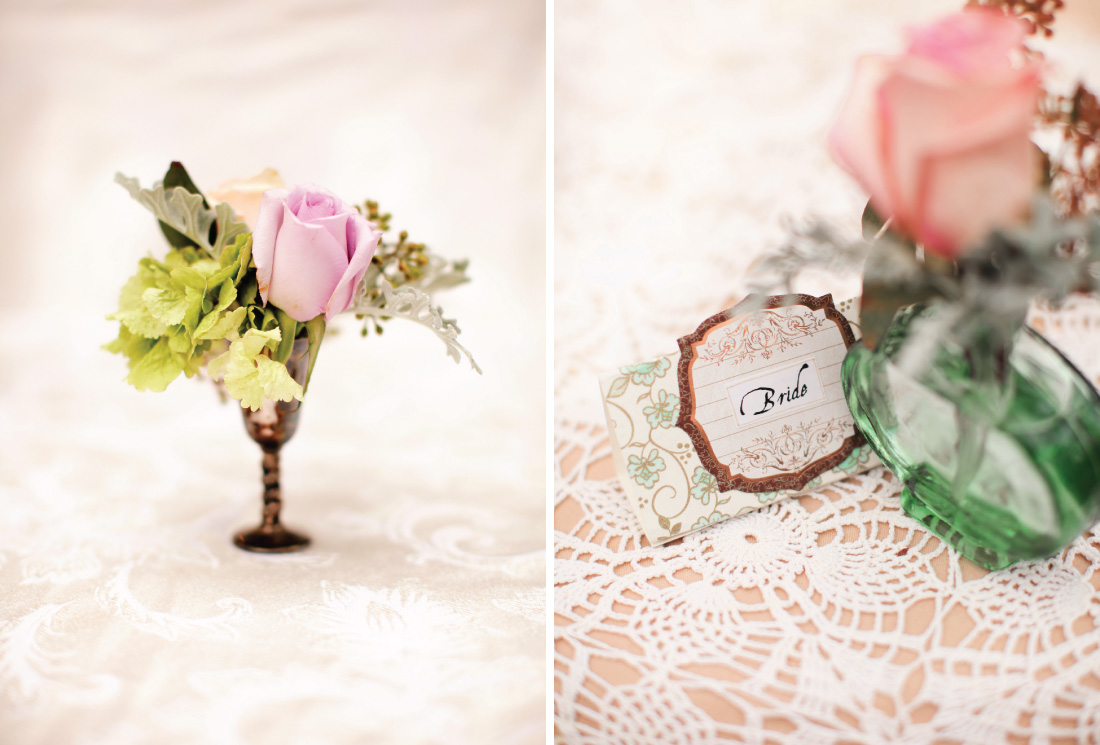 dainty floral arrangement in a tin cop, bride's name card next to a rose arrangement in a glass vase