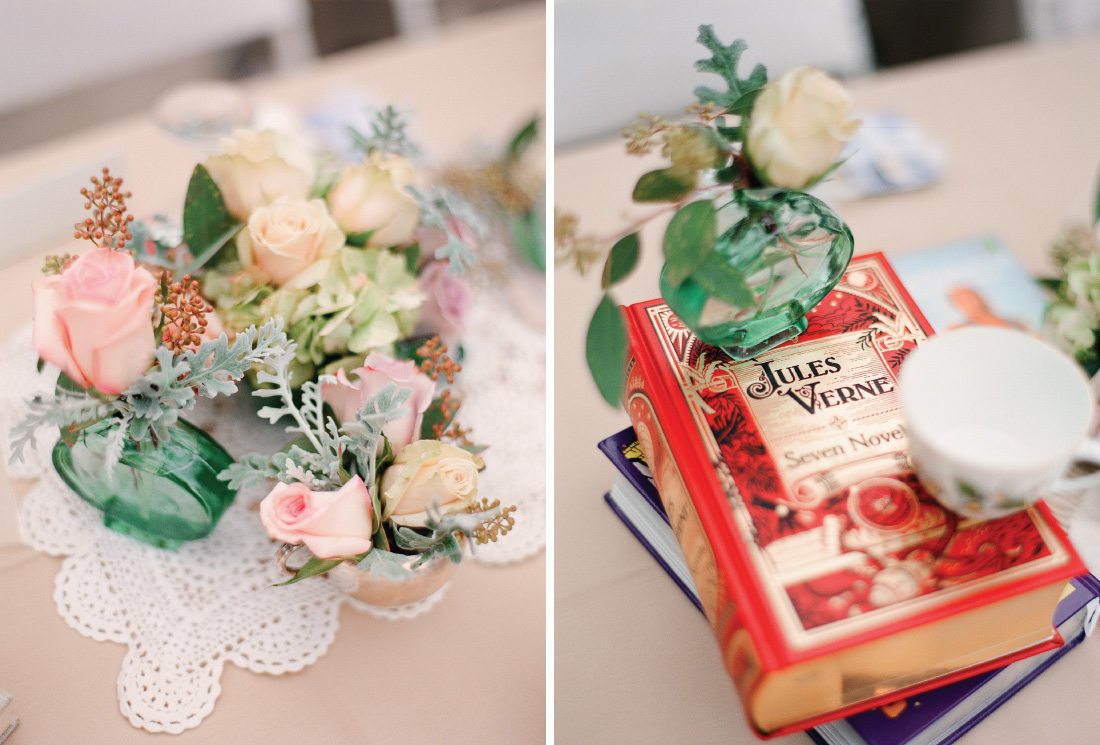cluster of dainty floral arrangements, dainty rose arrangement in a glass jar on top of a red cover Jules Verne book